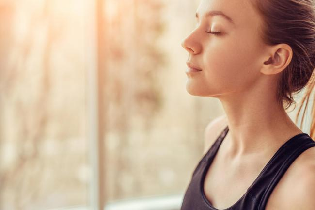 Side view of young female with closed eyes breathing deeply while doing respiration exercise during yoga session in gym.