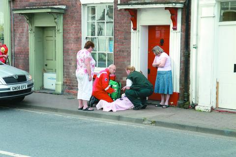 A paramedic and first responder treat a pensioner who fell in Market Street last week.