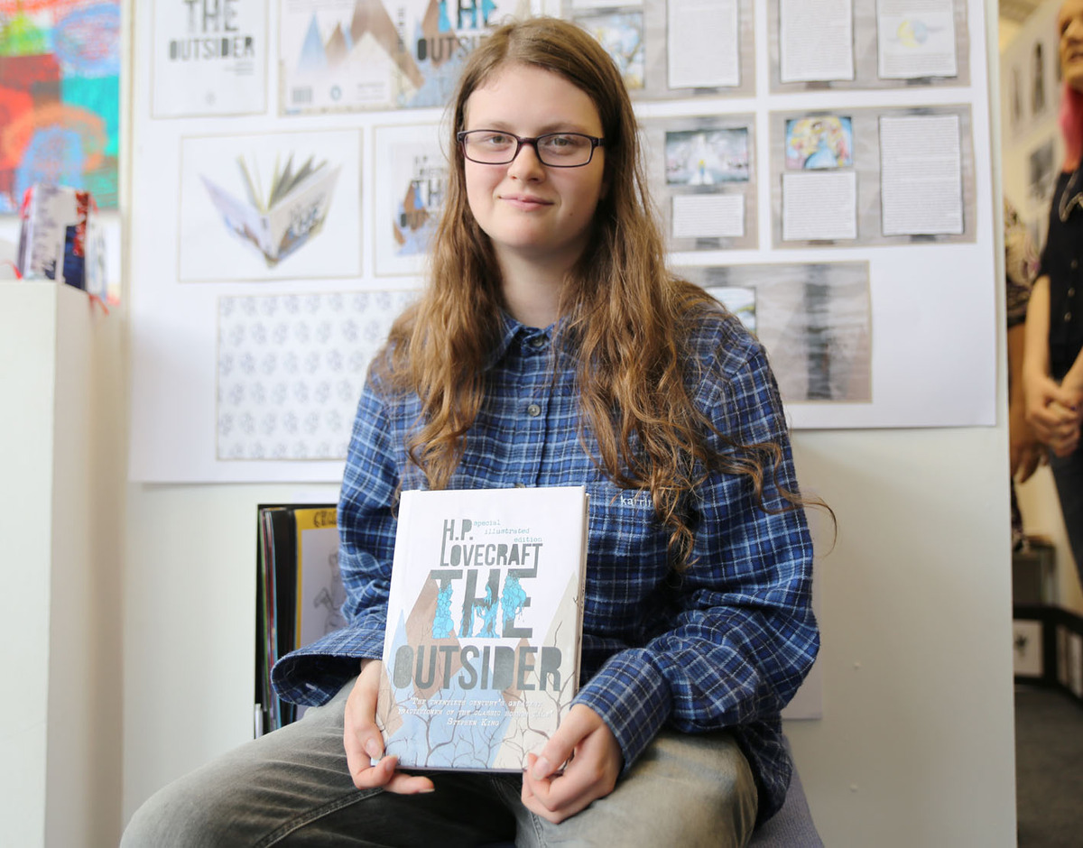 Ludlow College student Hannah Boar with a book of illustration.