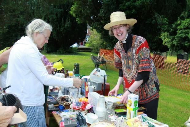 Ludlow Advertiser: Summer Fete at St Mary's Church, Tenbury. Rev Claire Lording helps out on the White Elephant stall wearing her straw hat ready to deal with the hot sun  Photo: Keith Gluyas (7401774)