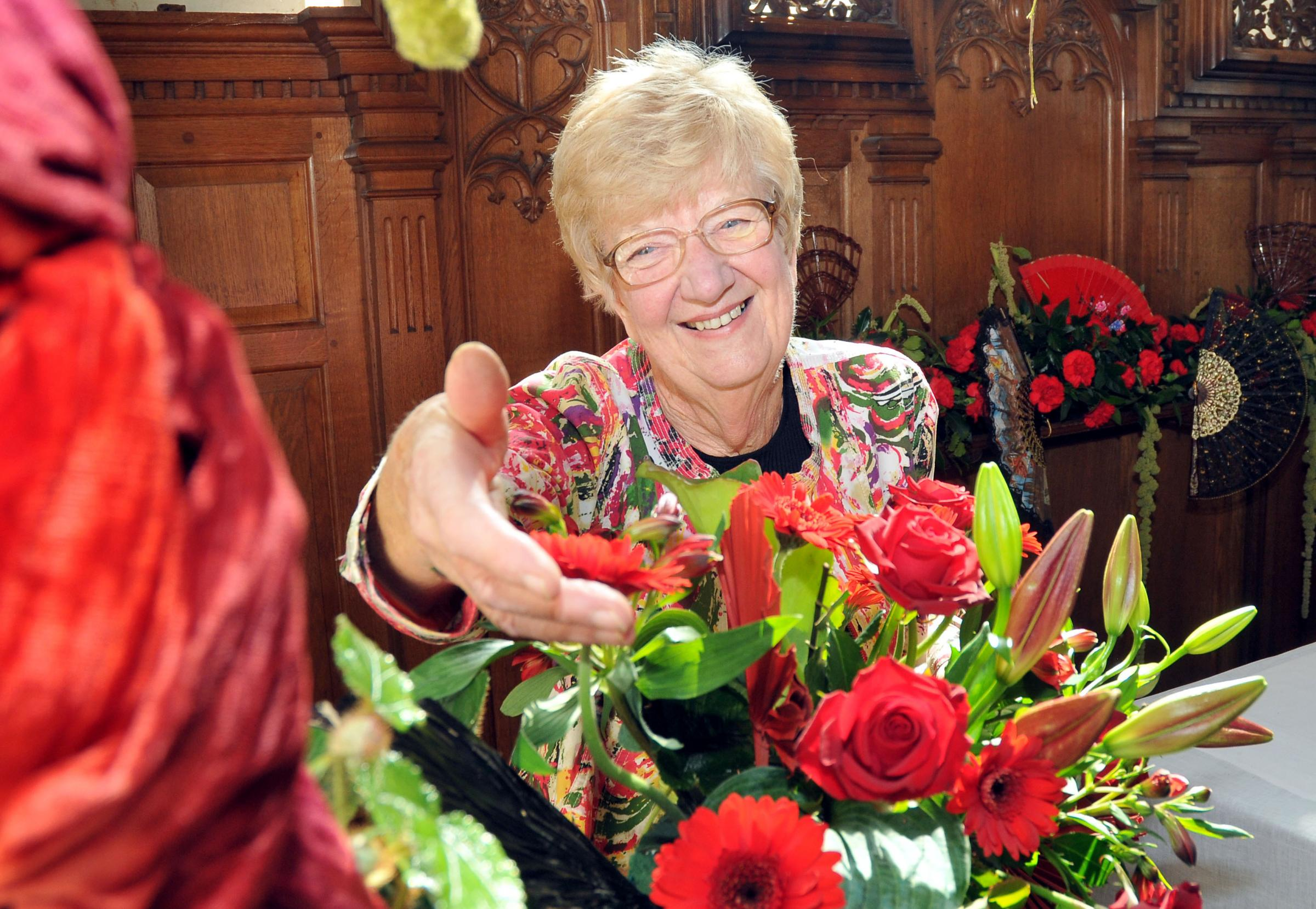 One of Stokesay Flower Festival oganisers Dorothy Crook admires some of the blooms on display.