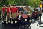 Tenbury Firefighters from left are: Ashley Morris, Ollie Tizorros, Milo Jackson, Ian Bowkett, young helper five-year- old Ellie Bowkett, helper Chantelle Pelka, Neil Lillwall and David James at the sponsored car wash  1519_5003 Photo: Andy Compton