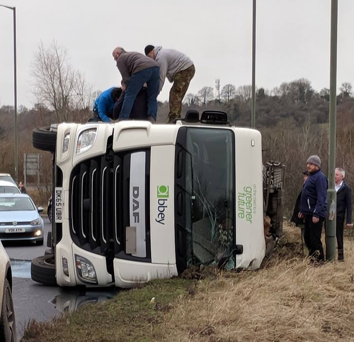 Dominic Everard (grey top and green trousers) and Mark Wosencroft (blue trousers) help to pull the injured driver from the lorry on the A49. Photo: Alec Osborn
