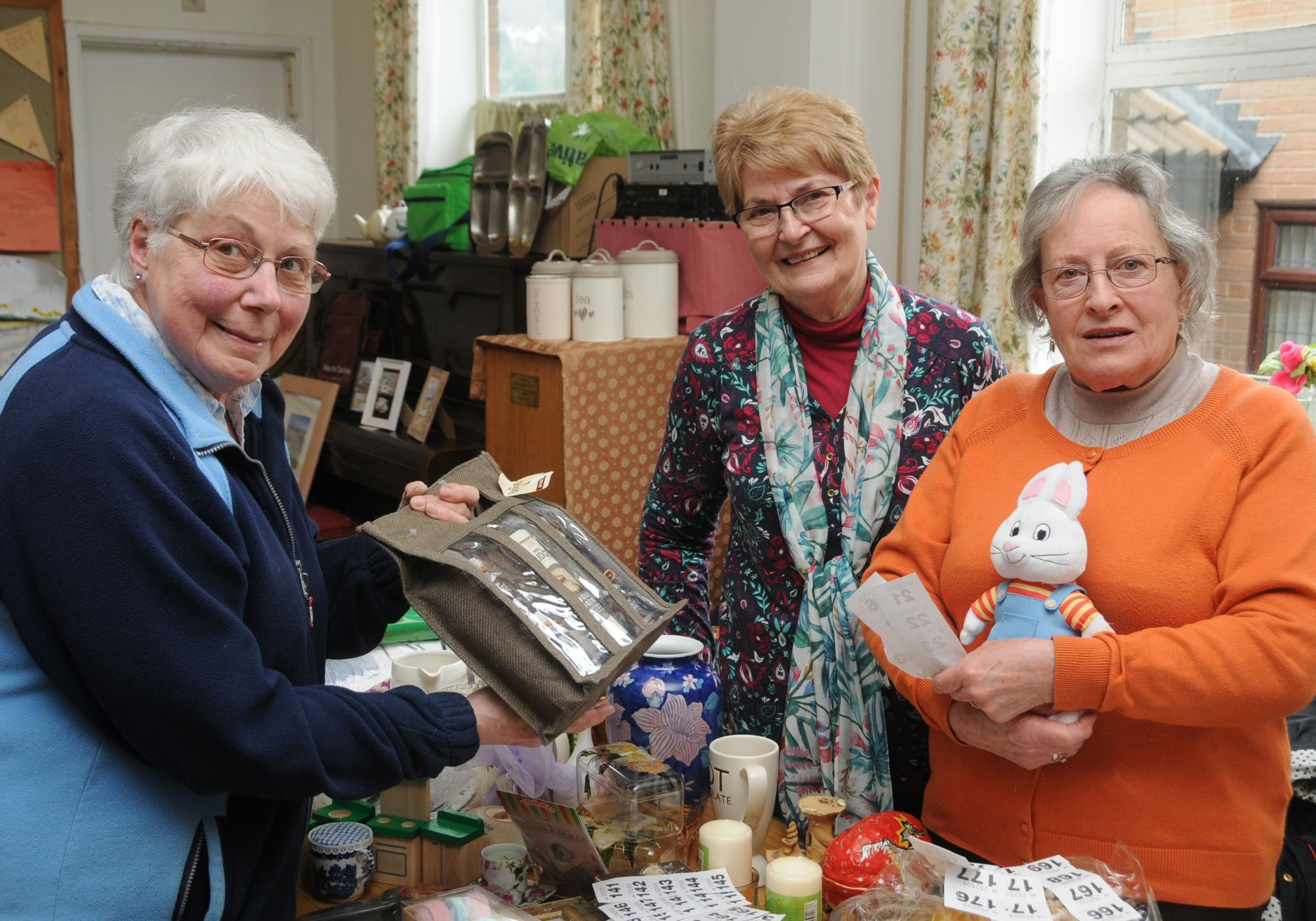 Reverend Hazel Ratcliffe shows Linda Roberts and Jan Edwards the raffle prize she has won.