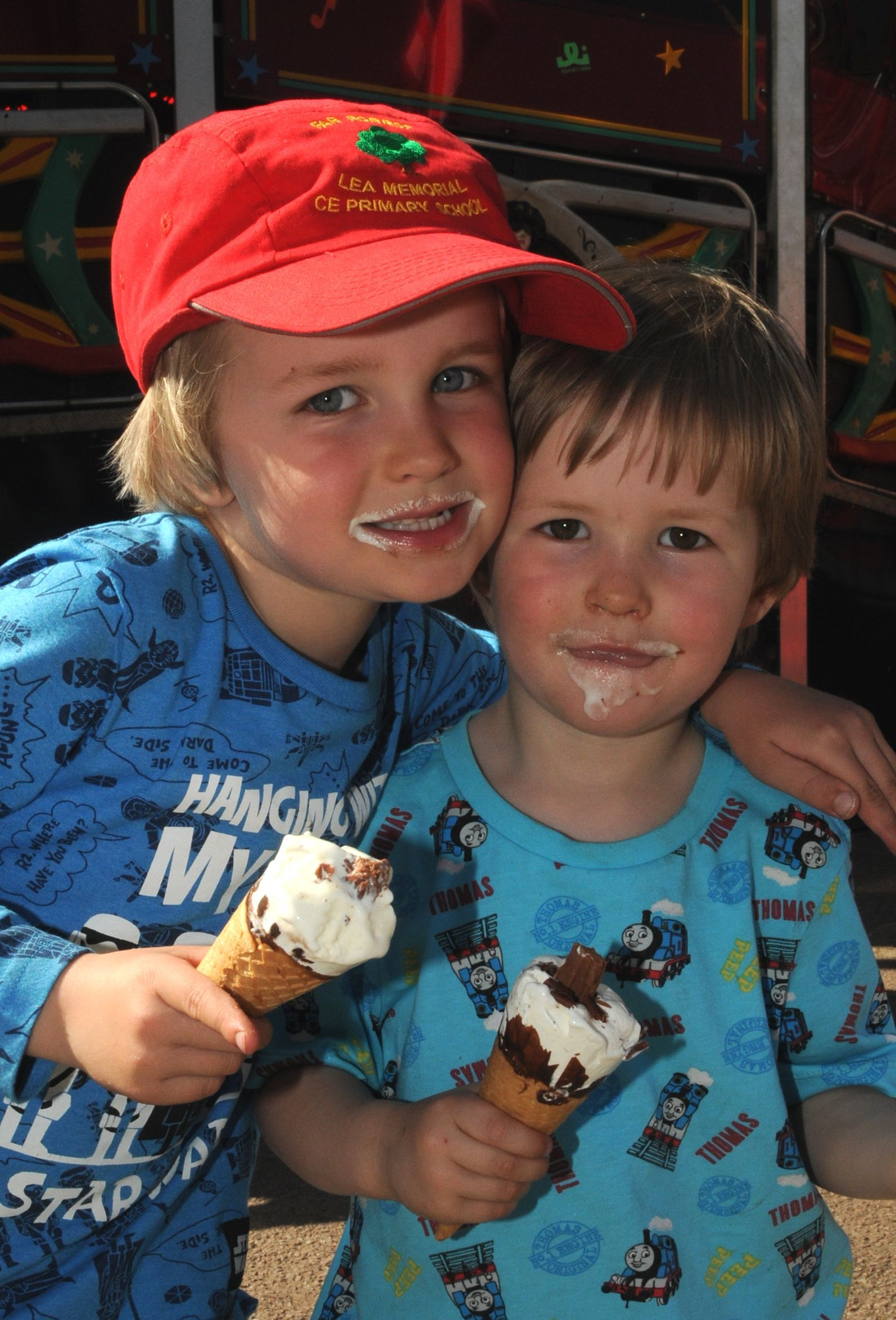 Five year old Freddie Norman gives his three year old brother Harvey a cuddle as they eat their ice cream at the fair.